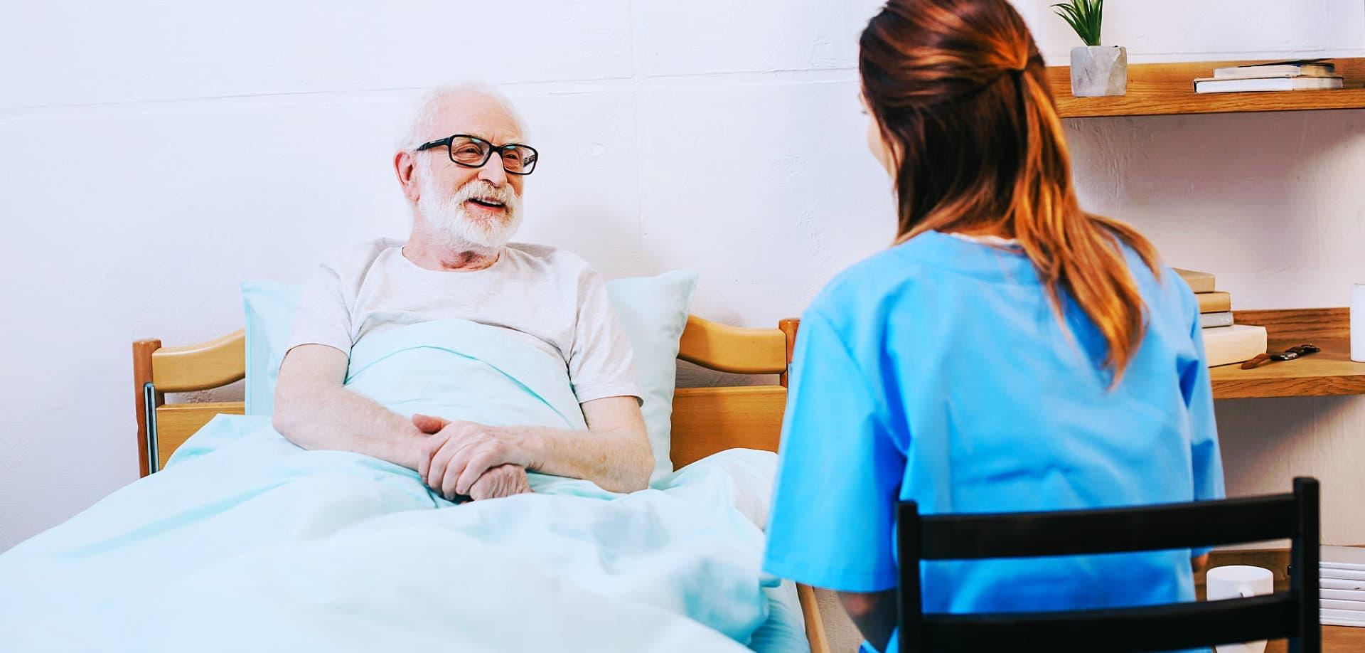 elder man in bed with caregiver