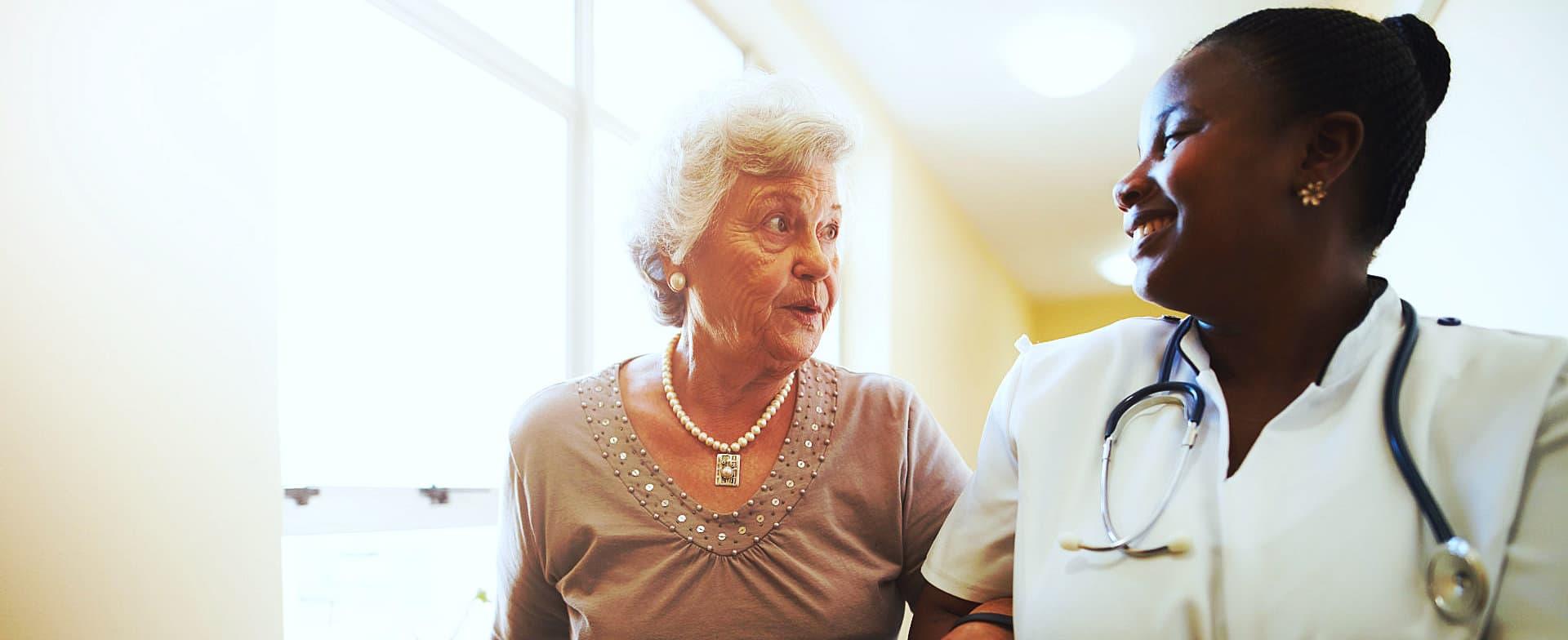 caregiver with elder woman on a hallway