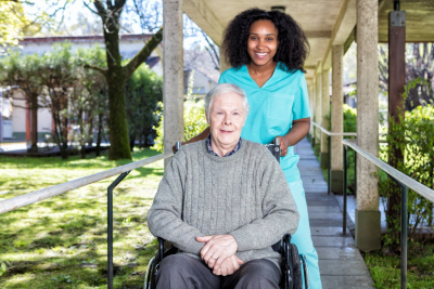 caregiver and senior woman outside senior home