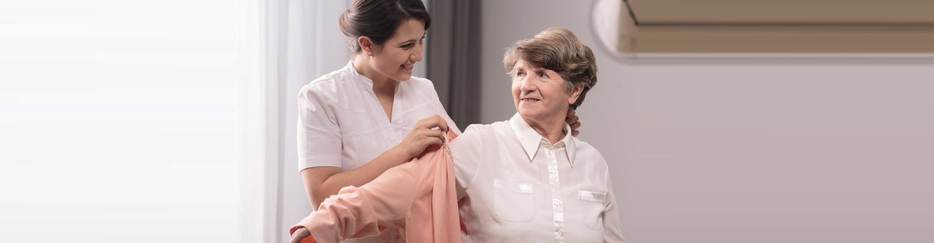 caregiver helping elder woman in wearing a shirt